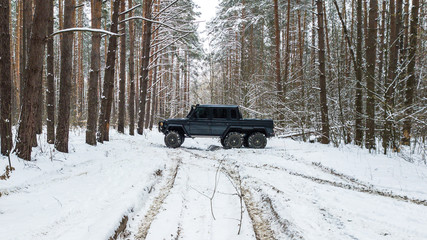 View on SUV 6x6 that rides by winter road in snow-covered forest
