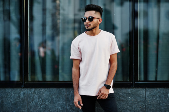 Stylish indian beard man at pink t-shirt, sunglasses. India model posed outdoor at streets of city.