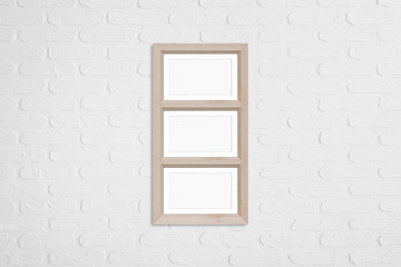 Wooden photo frame for three pictures collage on white bricks wall. Home, office, studio or gallery interior decor mock up