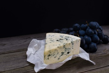 Blue cheese/Roquefort with fresh grape on white paper. Fruits, cheese, top view. Delicacy food.