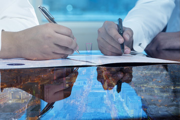 Businessmen hands signing documents on Riyadh skyline city scape background