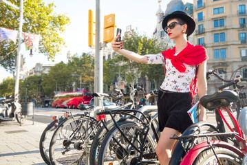 Woman taking selfie self-portrait on smartphone on the street in Barcelona