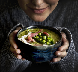 Woman holding a bolw filled with green pea soup