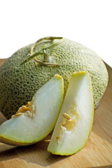 Fresh sweet green melon on the wooden board, tasty melons sliced on wooden board. Cantaloupe melon.