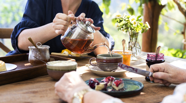 Daughter pouring hot tea for mother