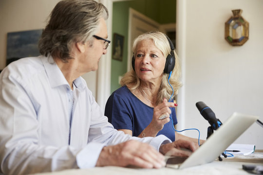 Senior woman wearing headphones and using microphone while discussing with male friend during vlogging at home