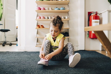 Girl sitting on carpet wearing shoes against rack in cloakroom at child care