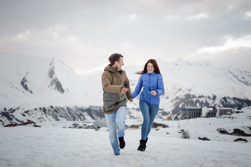 Young and happy lovers on the winter vacations spending time in mountains