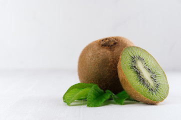 Juicy fresh kiwi with slice, leaves closeup on white wooden background, copy space, closeup. Elegance light soft fruits backdrop.