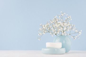 Bathroom interior - ceramic accessories - light blue circle vase, soap with white flowers on white wood table.
