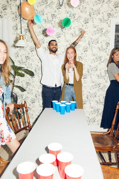 Cheerful young man standing with arms raised by female friend at dinner party