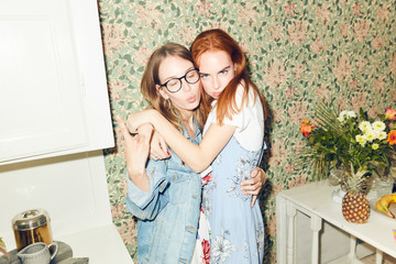 Portrait of young redhead woman embracing female friend showing horn sign at home