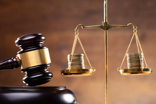 Close-up Of Gavel And Stacked Coins On Justice Scale