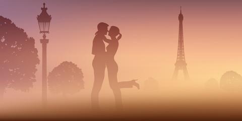 A Paris, un un couple d'amoureux au Champ de mars, s'embrassent devant la Tour Eiffel par un matin de brume