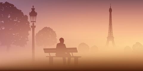 A Paris, un homme médite seul au Champ de mars, assis sur un banc devant la Tour Eiffel par un matin de brume