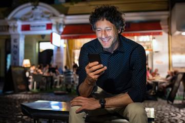 Mature happy man using phone at night