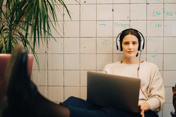 Portrait of confident young female computer hacker listening through headphones while sitting with laptop against tile w