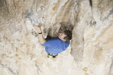 Young man looking up while climbing challenging route on cliff.
