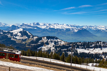 view of alpine train running in beautiful alps mountain switzerland europe on calm sunny day