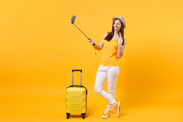 Happy tourist woman in summer casual clothes, hat doing selfie shot on mobile phone isolated on yellow orange background. Passenger traveling abroad to travel on weekends getaway. Air flight concept.