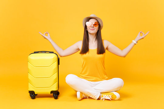 Traveler tourist woman in summer hat sit with suitcase crossed legs, meditate spread hands, isolated on yellow orange background. Passenger traveling abroad on weekends getaway. Air flight concept.