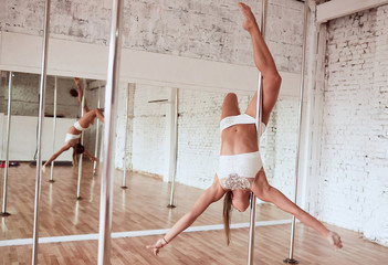 Woman crosses her legs around the pole while she dances in the studio