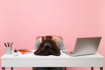 Young frustrated exhausted woman laid her head down on the table sit work at white desk with contemporary pc laptop isolated on pastel pink background. Achievement business career concept. Copy space. Wall mural