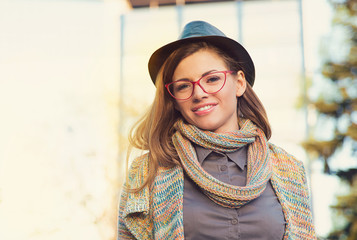 Beautiful young woman in hat and glasses