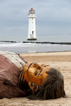 One of Royal Deluxe's giant marionette puppets lies on the beach at New Brighton