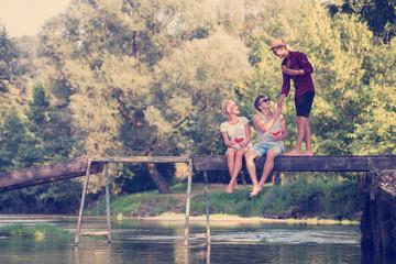friends enjoying watermelon while sitting on the wooden bridge