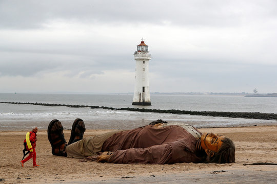 A lifeguard passes one of Royal Deluxe's giant marionette puppets as it lies on the beach at New Brighton