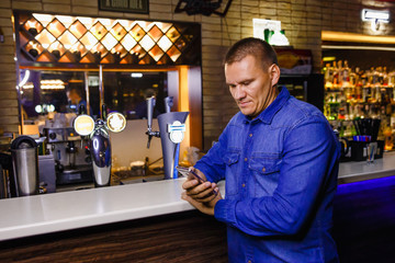 man looks into the phone behind the bar