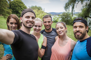 sportive friends take a group selfie after their hard workout in the city park next to the sea