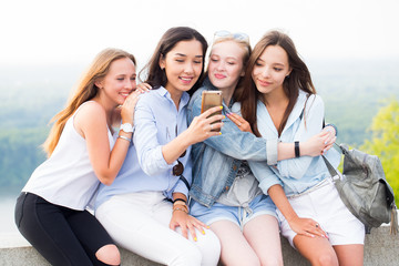 Four beautiful young women using smartphone and smiling in the Park, outdoor