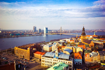 Panoramic view of old town with bright colorful houses and Riga Dome Cathedral, bridge over Dvina river in Riga, Latvia. Beautiful cityscape, top view.