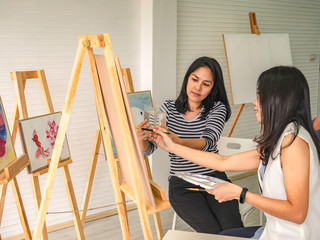 Two young asian woman artist dawning while useing ideas to think and create the best artwork together,fish concept