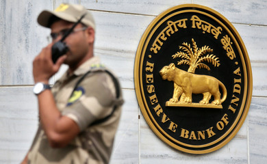 A guard stands next to the Reserve Bank of India (RBI) logo outside its headquarters in Mumbai