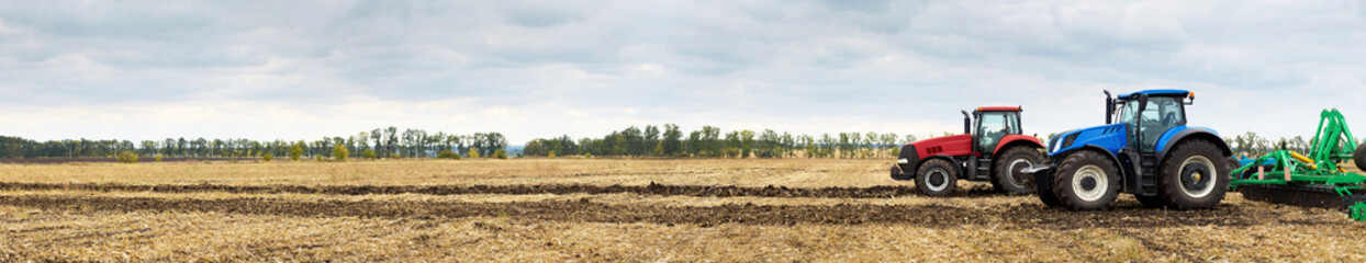 Two tractors with plows working in the field