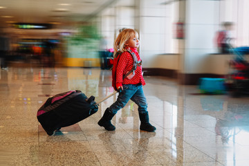 little girl with suitcase travel in airport