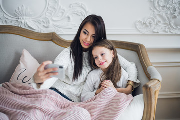 Happy mother and daughter taking funny Christmas selfies at home