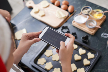Unrecognizable woman holding smartphone and taking picture of raw cookies lying on baking sheet on kitchen table