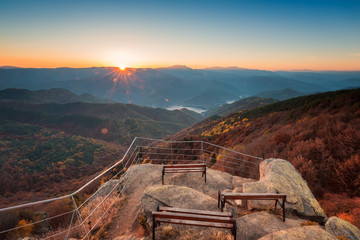 Autumn view from the top / Beautiful panoramic skyline autumn view with hilltop benches and colorful sunrise above an autumn forest in Rhodope Mountains, Bulgaria.