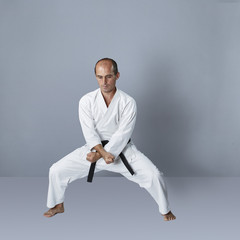 Active young athlete performs formal karate exercises
