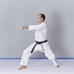 On a gray background, a young active athlete does formal karate exercises.