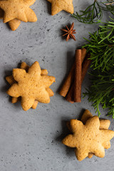 Traditional Christmas gingerbread cookies and juniper branch with Christmas decor on grey concrete background. Copy space for text.
