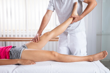 Male Therapist Stretching Woman's Leg