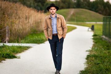 Handsome elegant man in the park wear jacket and fedora hat.