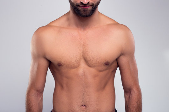 Perfection. Part of handsome shirtless young man standing against white background