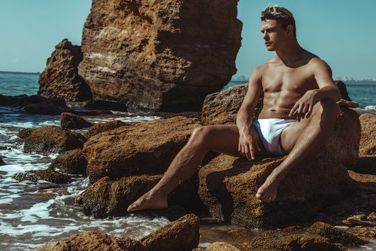 Strong face muscle male model on the nature background with sand stones and water on the beach on the sunset