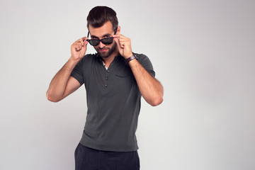 What I see here? Handsome young man in sunglasses looking at camera while standing against white background